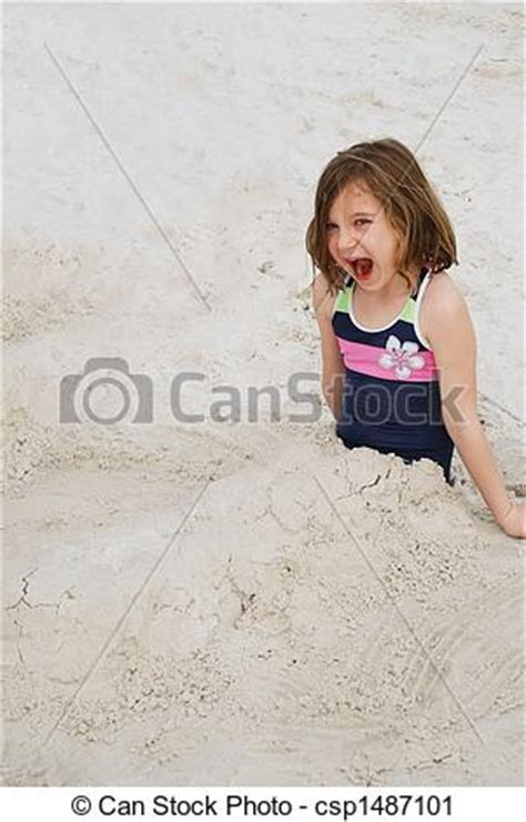 A happy little girl buried in the sand on the beach stock