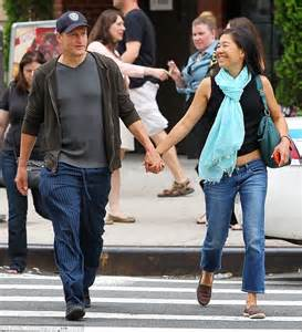 Woody Harrelson grins as he walks hand in hand with his